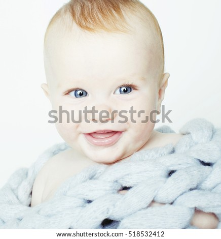 Stock Photo little cute red head baby in scarf all over him close up isolate