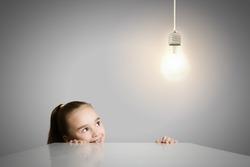 Little cute school girl and electric bulb