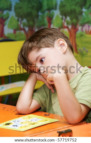 Little cute thoughtful boy playing game in kindergarten