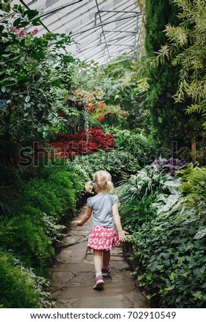 Little cute white Caucasian girl walking on stone path in botanical garden greenhouse with green trees, plants and colorful flowers around. Kid studying learning nature. Early development education