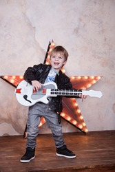 little cute 4 years boy playing guitar and singing like a rock-star