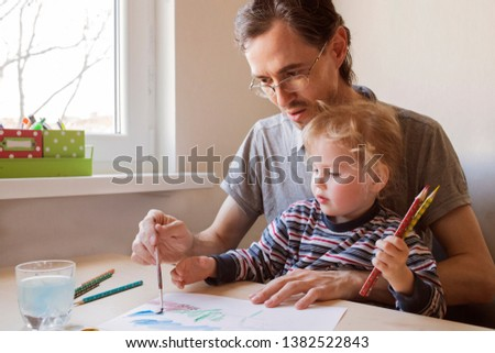 Little daughter and father draws a brush with fully happiness moment, concept of learning activity for kid in family lifestyle. Daughter sitting by her father on her lap. #1382522843