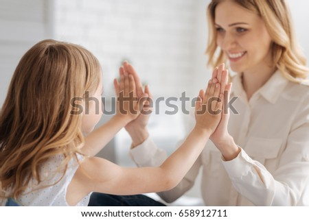 Little daughter comparing her hand size with mums #658912711