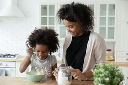 Little daughter helper and African mother cooking together in kitchen, kid girl preparing cake or pancakes enjoy process mixes dough using whisk, teach and upbringing, healthy home food, hobby concept