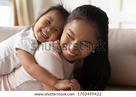 Little daughter piggybacks her Asian mother family play on couch in living room, close up. Excited mom laughing enjoy funny time together with preschool kid at home, have fun, happy motherhood concept stock photo