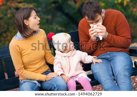 Little daughter sitting on bench in autumn park and  looking in her daddy who has a cold. Family health, colds, fall epidemics and virus epidemics #1494062729