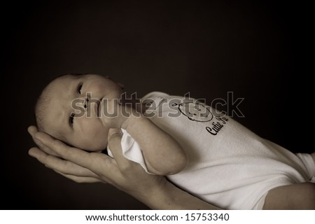 Little 7 days old baby lying securely on mom's arms, against a black background