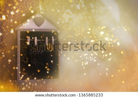 Little decorate wooden house with black copy space ahd small clothespins on the golden shining sparkling background. White words Love is on the writing board.