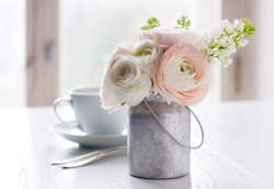 Little delicate elegant bouquet of flowers, buttercups and white lilacs in tin can and a teacup on white wooden table, morning breakfast