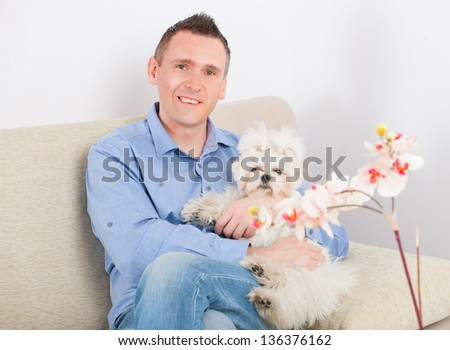 Little dog maltese sitting with his owner on the sofa in home