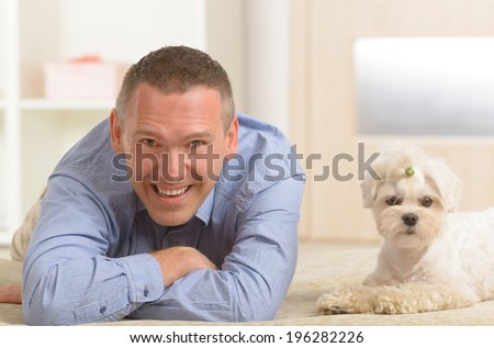 Little dog maltese with his owner on the sofa in home