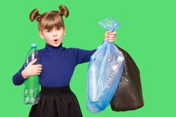 Little ecologist girl with confused funny face holding trash bags with plastic bottles isolated on green background. Ecology environment problem consumption