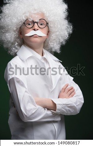 Little Einstein Confident little boy looking like Einstein and standing isolated on black