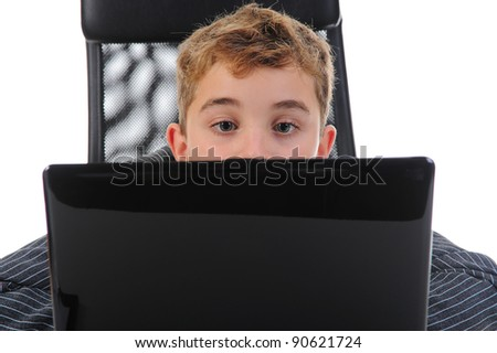 Little emotional boy sits at a computer at a desk in a bright office. Isolated on white background