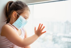 Little european girl wearing mask for protect pm2.5 and Covid-19. Sick child Little girls look at the window with longing on the street . Copy  space. sadness child at home in isolation