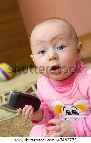 little european surprised eight months old girl holds cell phone and looks into camera