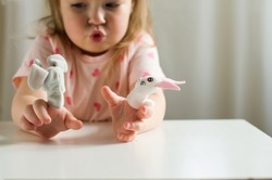Little expressive girl playing theater with animal finger puppets. Role-playing games and activities have the potential to improve language skills, creativity, social awareness, emotional development