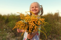 Little fair-haired girl holding a bouquet of yellow flowers on a background of sky and grass