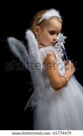 Little fairy with a magic wand on a black background.fairy-tale.Christmas.