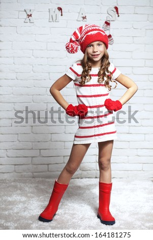 Little fashion girl in fashion Christmas clothes posing over white brick background, full length