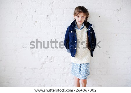 Little fashion girl in fashion  clothes posing over white brick background
