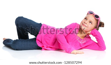 Little fashion girl lying in pink dress and sunglasses. Isolated white backround.