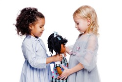 Little fashionable girls are friends of two different nationalities. African American girl showing doll to her friend