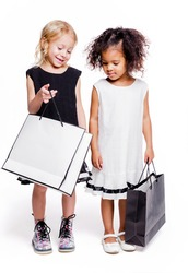 Little fashionable girls of two different nationalities are posing against a white background with bags from the store. One girl shows the other what is in her bag
