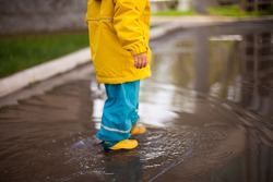 little feet of a child in rubber boots and a waterproof suit walk on the water. puddles on the pavement breathe fresh air in any weather. close-up without face
