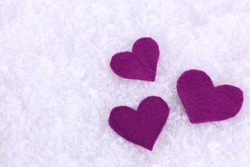 Little felt hearts on snowy background