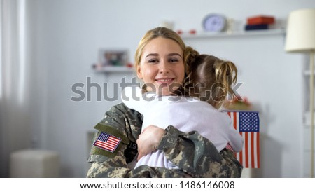 Little female kid with US flag embracing soldier mother, family reunion, patriot