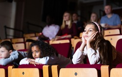 little female viewer sitting at premiere in theatrical hall