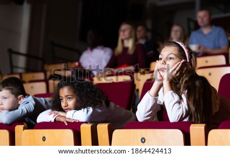 little female viewer sitting at premiere in theatrical hall ストックフォト ©