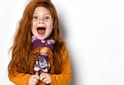 Little five-year-old red-haired girl happy screaming yelling. Child kid holds a red hair doll in her hands in an orange sweater on white background