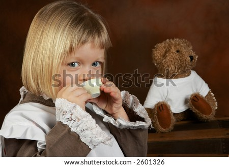Little four year old drinking tea with her teddy bear