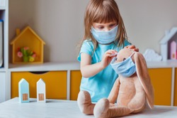 Little four years old girl in the face mask wearing her rabbit soft toy in the same mask in the kids room. Social distance stay at home during Covid-19 Pandemic concept.