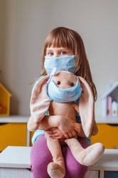 Little four years old girl wearing face mask holding bunny soft toy in the same mask in the kids room. Social distance stay at home during Covid-19 Pandemic concept.