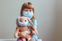 Little four years old girl wearing face mask holding rabbit soft toy in the same mask indoor. Social distance stay at home during Covid-19 Pandemic concept.