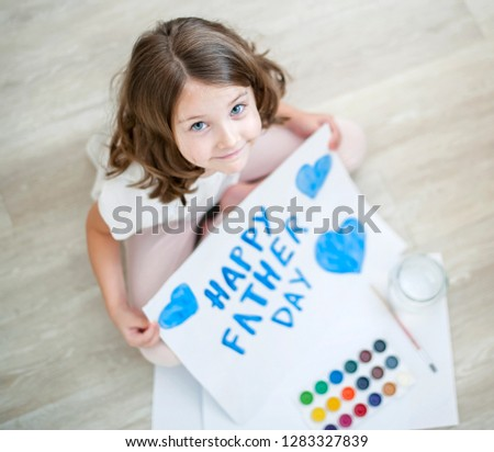 Little fun caucasian girl sitting on floor at home. Looking at camera. Cute kid paints a blue heart  on a homemade greeting card. Father Day. Traditional play concept. Arts and crafts. Top view