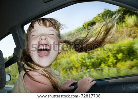 Little fun girl speeds in car near the open window.