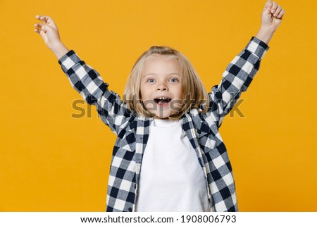 Little fun happy kid boy 4-5 years old wears casual clothes celebrating win raised hands up isolated on bright yellow wall color background children studio portrait. People childhood lifestyle concept Сток-фото ©