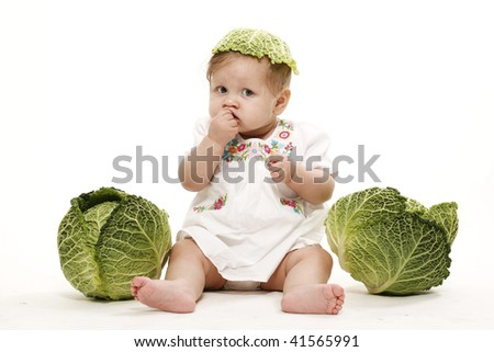 Little funny baby girl with cabbage