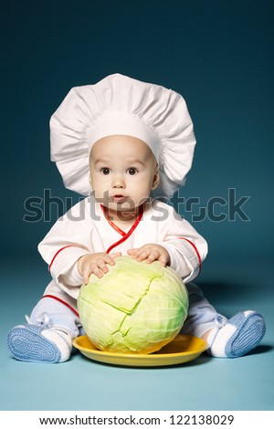 little funny baby with cook costume holds cabbage