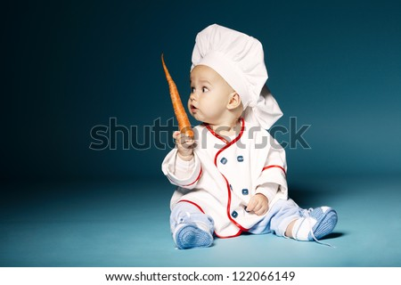 little funny baby with cook costume holds carrot
