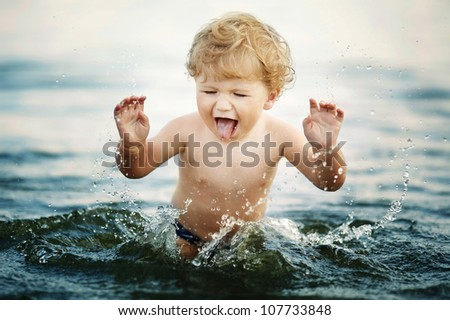 little funny boy playing in water