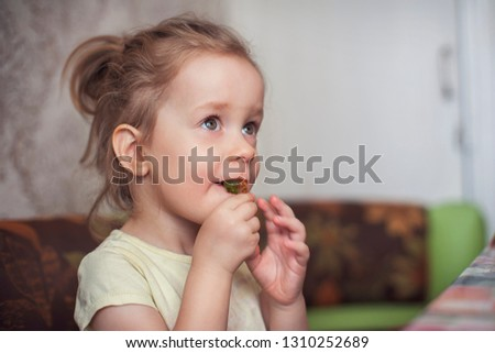 Little funny girl eats marmalade closeup portrait #1310252689