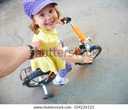 Little funny girl learning to ride a bike