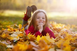 Little funny girl lies on yellow leaves in the forest. Child on a walk in the autumn park. Preschool girl on the street