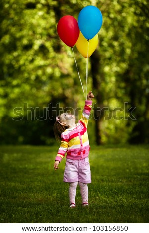 little funny girl plays with balloons in park