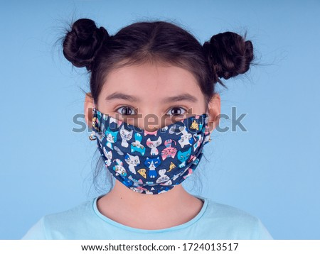 Little funny girl with a collorful mask. Excitement and fascination concept. Close up portrait. Coronavirus blue background. foolish grimaces comical crazy gesture. Funny expression. Covid-19.